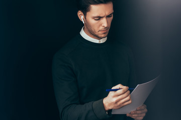 Portrait of pensive young handsome man have a conversation with colleagues during meeting with wireless earphones. Businessman using wireless headphones in business conference making notes on paper.