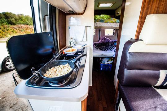 Cooking dinner or lunch in campervan, motorhome or RV. Preparing chicken  in a pan in camper van when traveling with RV, motor home caravan or motorvan. Vanlife or van life lifestyle on the road.