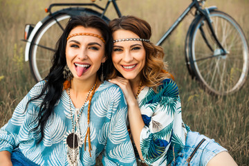 Two cute beautiful hippie girls outdoors ride a bike, have fun, laugh, dressed in denim shorts, shirts, accessories, bracelets, necklaces, earrings, curly hair, bohemia, indie, boho style, summer