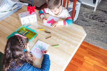 Two children drawing greeting cards for mother's day