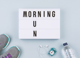 Set for sport activity: running shoes, headphones, bottle of water and alarm clock on gray background, top view flat lay. Healthy life style concept