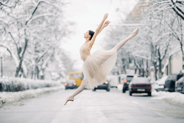 Beautiful ballerina is dancing and jumping on snowy street among cars.