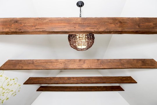 Stained brown decorative wooden beams in home living room white color ceiling. Brown round rattan lamp illuminated.
