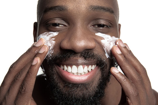 Young african-american guy applying face cream under his eyes on white background. Portrait of a young happy smiling african man at studio. High fashion male model.