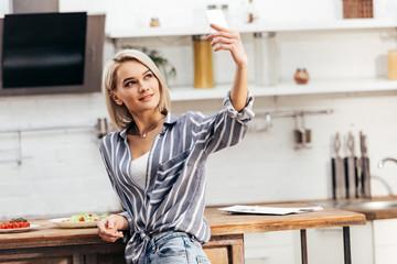 attractive woman taking selfie near table on kitchen