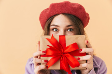 Image of brunette woman 20s with long hair smiling and holding gift box, standing isolated over beige background