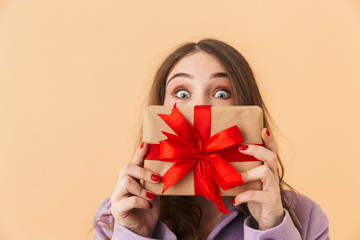 Image of surprised woman 20s with long hair smiling and holding present box, standing isolated over beige background