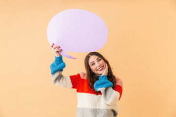 Portrait of attractive woman 20s holding blank thought bubble above her head, copyspace for your text, while standing isolated over beige background