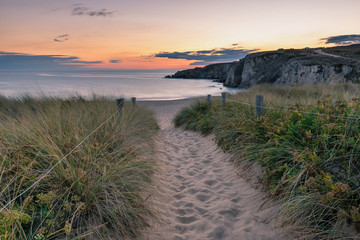 French landscape - Bretagne. A beautiful beach with dunes and  wild cliffs in the background at sunset.
