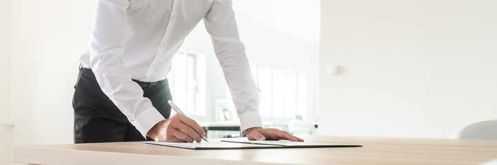 Wide view image of businessman signing a document