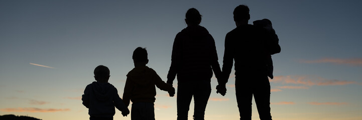 Silhouette of a family of five standing under the evening sky