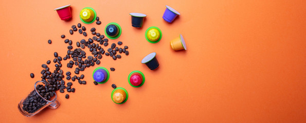Coffee beans and a glass cup, on orange color background, copy space