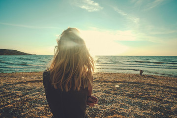Girl looks on the sea. Dreary blonde girl looks at the sea. Sad for a loved one alone.