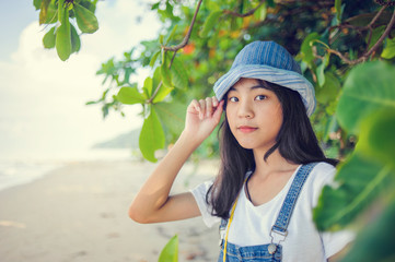 a young attractive asian woman standing on the ocean beach with .dungarees dress