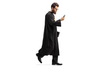 Priest walking with a mobile phone