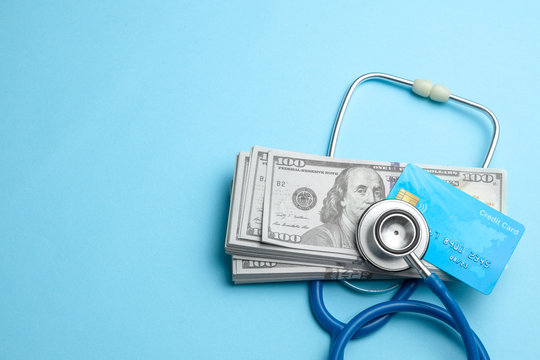 Stack of cash dollars and credit card with stethoscope on blue background. The concept of medical strechevka or expensive medicine, doctors salary.