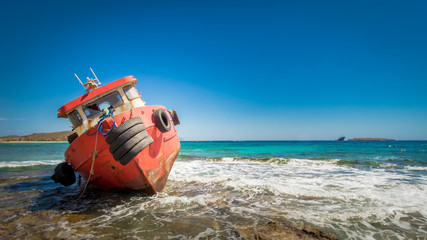 Nice red coloured shipwreck stranded on a rocky beach, with a background of a turquoise sea and a blue sky,  located at the island Kythira,  Greece.