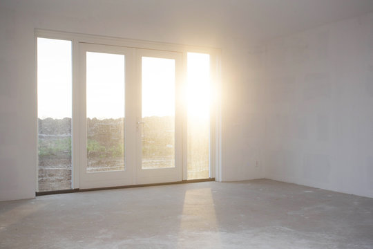 Empty room with big window , frame and double doorsnew construction, still in progress with sunlight shining