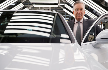 Adrian Hallmark, CEO of Bentley Motors, poses for a photograph next to one of his company's cars on the production line of their factory in Crewe
