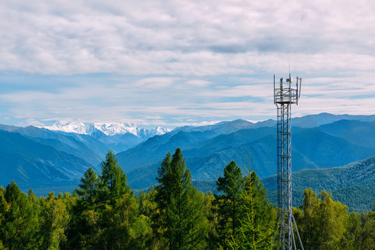 Telecommunication cell tower in the wild forest with mountain background, Altay