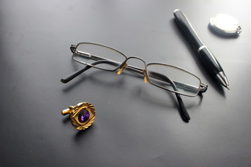 Still life, business, office supplies or education concept: a view of a recumbent padding, glasses, a pen, a clock, accessories against a dark background, ready to add or layout