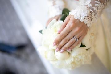 bridal hands on a wedding bouquet