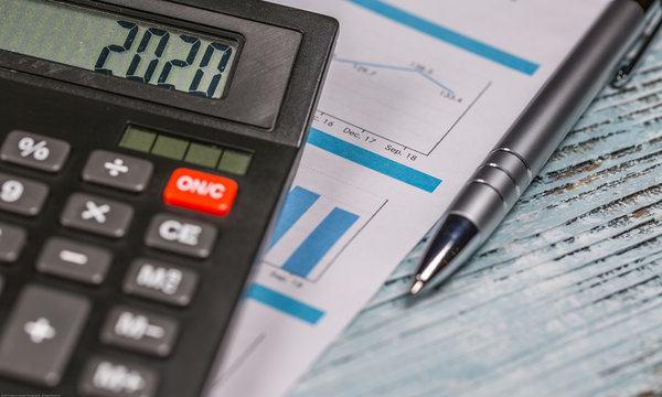 Calculator with 2020 digits lie on financial document with pen on the wooden table