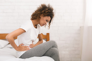 Unhappy woman suffering from stomachache, sitting on bed