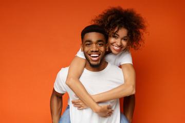 African-american couple having fun on orange background