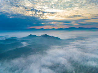 Aerial view of mountain and morning mist during sunrise.
