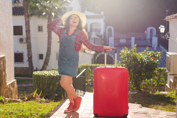 Journey, holidays and summer concept - young woman with red travel suitcase arrived in hotel