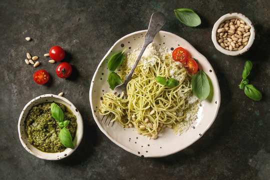 Classic italian spaghetti pasta with pesto sauce, pine nuts, olive oil and fresh basil. Served in ceramic plate with fork and ingredients above over dark metal background. Flat lay, space