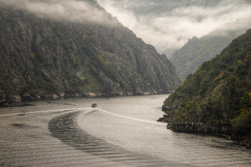 A ship enters a canyon of granitic cliffs