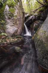 A stream forms a water jet between granitic rocks