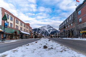 Cityscape view of Banff Avenue, a popular tourist destination in the Canadian Rockies, filled with gift shops and restaurants with Mt. Rundle in background