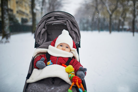 Baby girl in stroller in Paris on a day with heavy snow