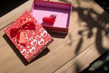 Single heart in lovely gift box on wooden texture background. Valentines day card concept. Heart for Valentines Day Background