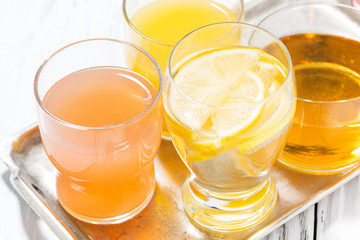 assortment of fresh citrus juices in glasses on white table, top view closeup