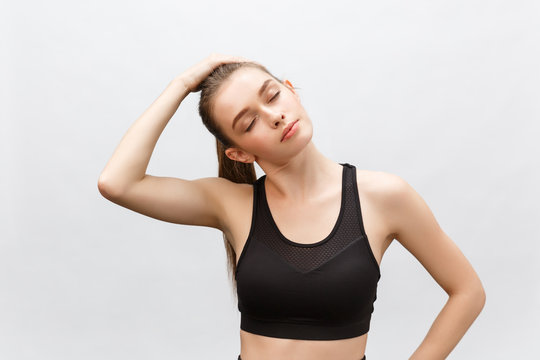 Young sporty beautiful woman stretching arms on side. Isolated over white background