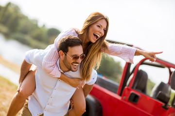 Young woman and man having fun outdoor near car