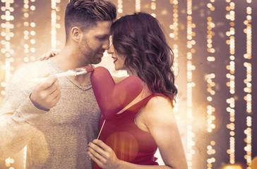 Festliches Bild von Pärchen mit Pinsel mal Herz an , Frau mit rotem Abendkleid und schöner Frisur