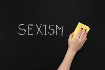 Sexism is written on chalkboard and hand with sponge