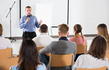 Male professor delivering speech to students
