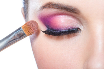 Close up of brush applying bright pink makeup on eye of pretty girl, isolated on white