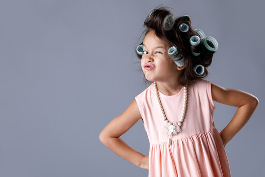cute little child girl in pink dress and hair curlers