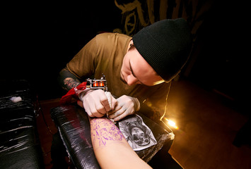 Handsome young guy in a black hat and with tattoos, beats a tattoo on his arm, tattoo salon, tattoo artist