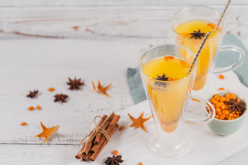 Two high glasses with colorful hot sea buckthorn tea with cinnamon sticks, anise stars and fresh sea buckthorn berries