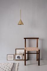 Modernes Interieur mit Stuhl und Messinglampe
