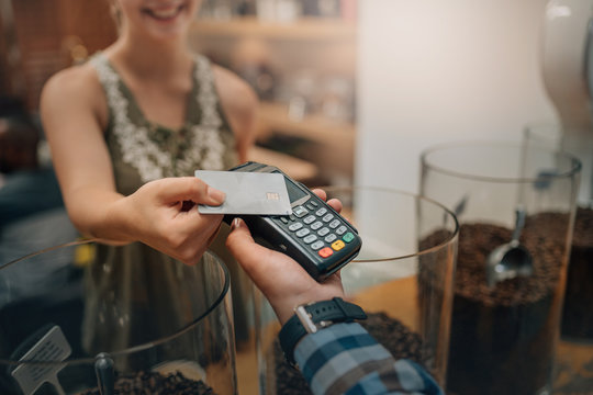 Hand of customer paying with contactless credit card with NFC technology. Waiter with a credit card reader machine and with female smiling holding credit card. Focus on hands