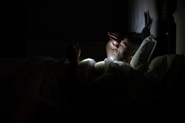 Man using his phone in his bed instead of sleeping, technology addiction concept
